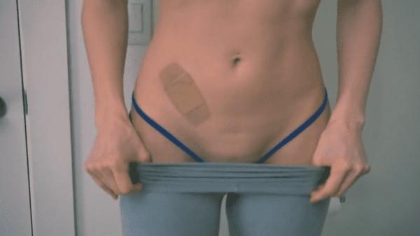 shirtless woman removing grey yoga pants to film tampon fetish
