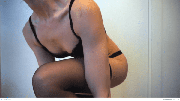 woman wearing black bra, black panties, and black stockings doing a panty try on