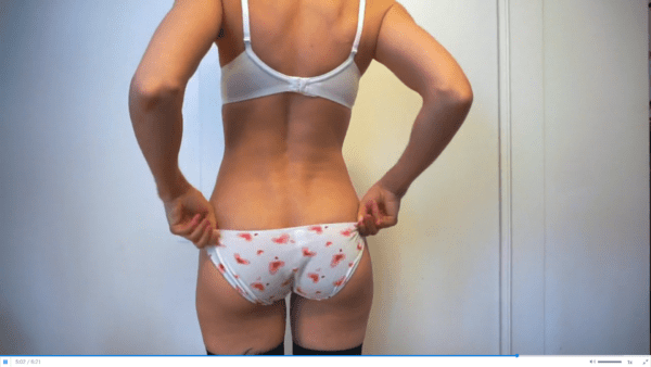 woman wearing white bra and white panties with pink hearts doing a panty try on
