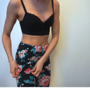 woman wearing black bra and flower leggings doing a panty try on