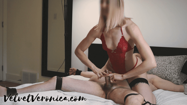 woman wearing red lingerie sitting on top of naked man tied to bed while she gives handjob before putting numbing cream on cock