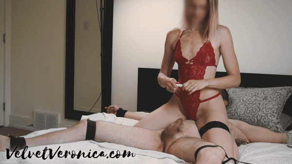 woman wearing red lingerie siting on top of naked man tied to bed putting numbing cream on cock
