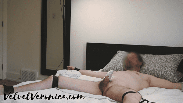 naked man tied to bed with numbing cream on cock