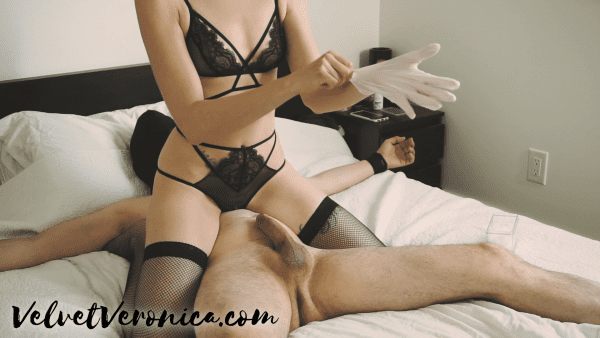 woman wearing black lingerie sitting on top of a naked man putting on a latex glove for his prostate massage