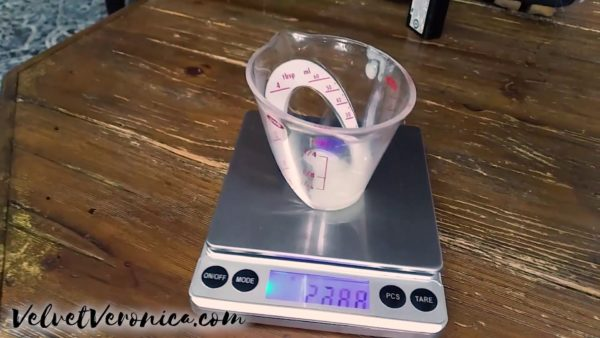 measuring cup with cum ejaculate being weighed on a scale